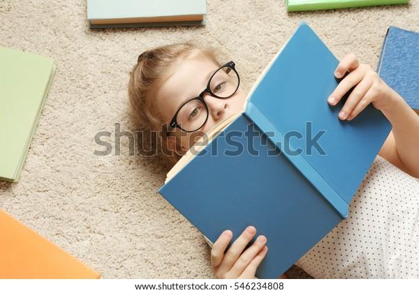 Pequeña y educada leyendo un libro mientras está echada en la alfombra