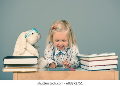 Cute little girl reading books to her rabbit friend. Educational concept.