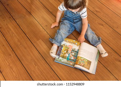 A cute little girl is reading a large thick book in a children's room or kindergarten. The child reads the merry book with interest. Child reading book on the wooden floor at home . Top view