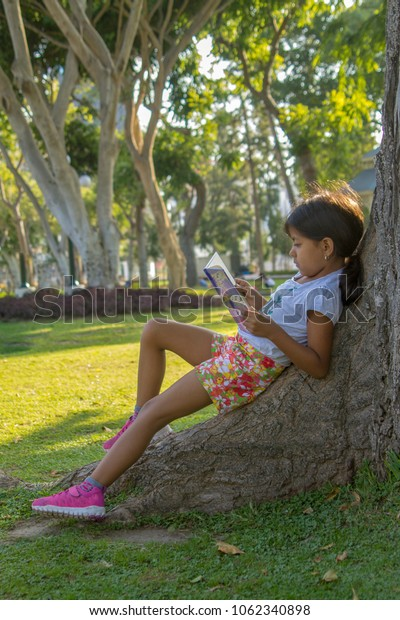 Cute little girl reading in the park