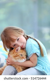Cute little girl with red cat on window background