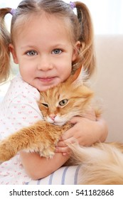 Cute little girl with red cat at home