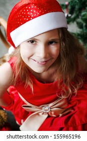 cute little girl in a red dress and in a hat santa claus sitting with a Christmas tree
