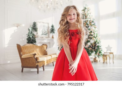Cute little girl in red dress celebrating cristmass at home