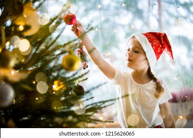 Cute little girl in red Santa hat and plaid skirt decorating Christmas tree at home. Cozy living room decorated with lanterns and Christmas lights. Scenic winter view of pine trees in snow in window