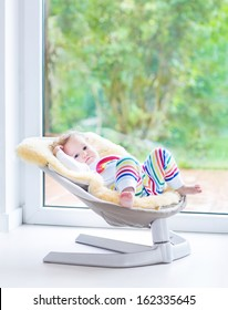 Cute little girl relaxing in a swing next to a big window
