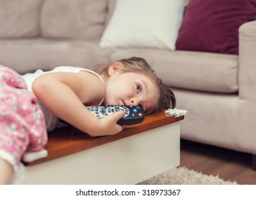 cute little girl with remote control lying on coffee table and watching tv