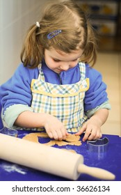 Cute little girl rolling dough for preparing Christmas gingerbread cookies