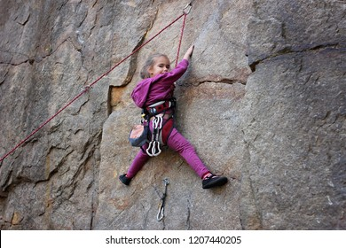A cute little girl with a rope engaged in the sports of rock climbing on the rock, outdoor extreme sport and active lifestyle, natural rock mountains