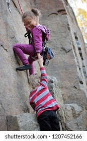 A cute little girl with a rope engaged in the sports of rock climbing on the rock stretching her hand to her little brother, outdoor extreme sport and active lifestyle, natural rock mountains