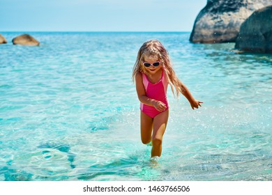 Cute little girl running in turquoise sea on beautiful tropical beach. Summer, beach fun and vacation concept