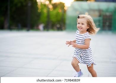 Cute kleine Mädchen läuft um den Platz in einem Stadtpark. Warmer Sommertag. Baby macht sehr viel Spaß.
