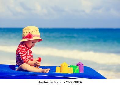 cute little girl  with sand toys on summer beach