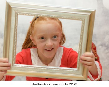 Cute little girl in a Santa Claus suit looking through a frame smiling at the camera