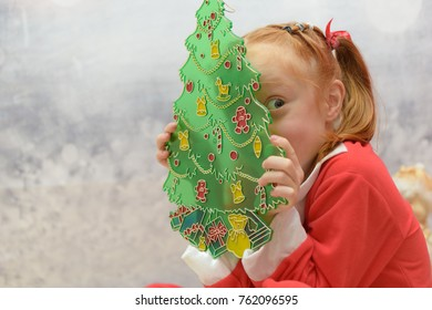 Cute little girl in Santa Claus suit hiding behind a Christmas tree decoration