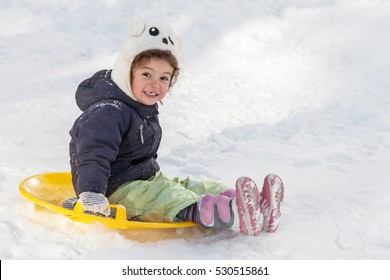 Cute little girl with saucer sleds outdoors on winter day, ride down the hills, winter games and fun