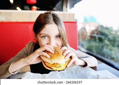 Cute little  girl in school uniform  eating a hamburger and potatos in the restaurant