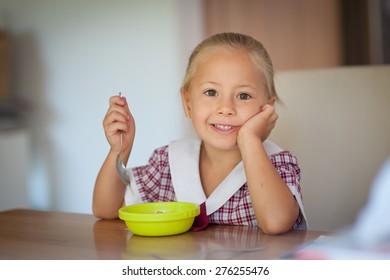 Cute little girl in school uniform having breakfast in the morning before school