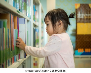 Cute little girl selecting book in the library, this image can use for education