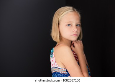 Cute little girl with a serious look on her face while her hands are close to her face.