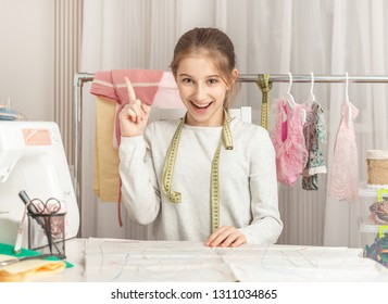 cute little girl in a sewing workshop examines pattern