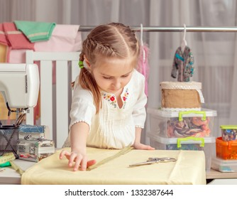 cute little girl in a sewing workshop measures the fabric