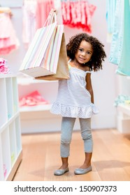 Cute little girl with shopping bags at the store