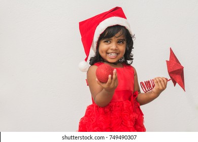 Cute little girl showing Christmas decorated items while she's smiling