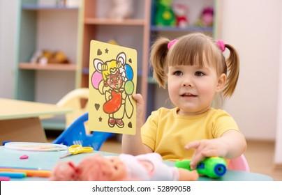 Cute little girl showing a picture in preschool