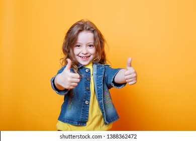 Cute little girl showing thumbs up on orange background