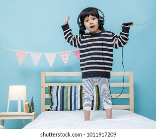 Cute little girl sing a song with smartphone in her bedroom, technology concept