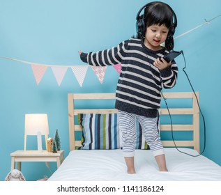 Cute little girl sing a song with smartphone in her bedroom, Happy asian child little girl listening the music with headphone on the bed