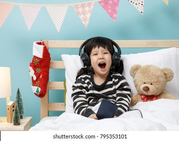 Cute little girl singing with smartphone with teddy bear in her bedroom, technology concept