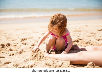Cute little girl sitting at the beach and burying her mother's feet with sand