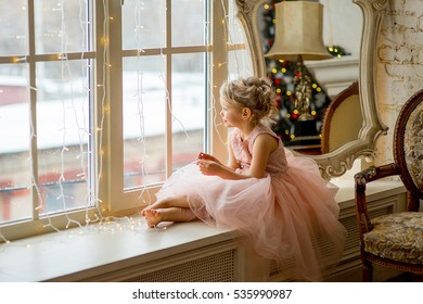 Cute little girl sitting by the window and looking at it. Mirror. Christmas. New Year