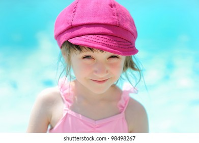 Cute little girl sitting by a swimming pool