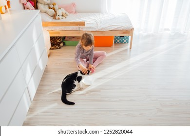 Cute little girl sitting with cat at home