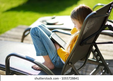 Cute little girl sitting in a garden and reading an ebook on sunny summer evening. Education for kids.