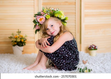 cute little girl sitting in her room on a white carpet with a wreath of flowers on her head