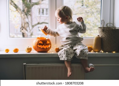 Cute little girl sitting near window with carving pumpkin head jack lantern at home. Family with child preparing decoration for Halloween.