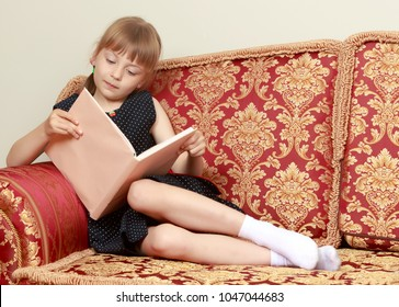 A cute little girl is sitting on the couch and reading a book. The concept of literature, school education and intellectual development of the child.