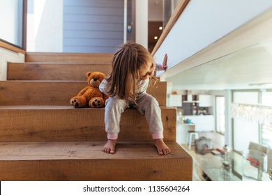 Cute little girl sitting on staircase and looking down through a glass wall indoors. Girl child peeking in living room from wooden stairway at home.