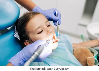 Cute little girl sitting on dental chair and having dental treatment.