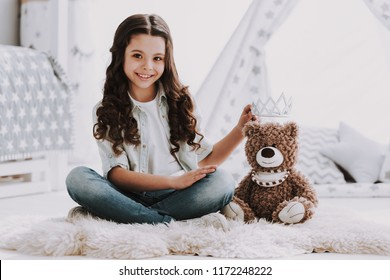Cute Little Girl Sitting on Carpet with Teddy Bear. Smiling Adorable Little Girl Sitting on Crpet next to Bed and Playing with Bear Toy at Home. Beautiful Little Girl in Bedroom. Childhood Concept