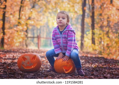 Cute little girl sitting on a carved jack o lantern