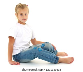 A cute little girl is sitting on the floor, wearing a clean white T-shirt and jeans. On the shirt you can put a logo or any other inscription. The concept of advertising on clothes, Happy childhood