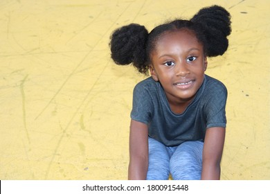 Cute little girl sitting on yellow background outdoors