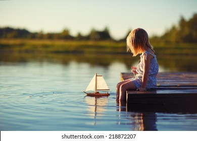 A cute little girl sitting on the pontoon bridge on the river with a toy ship in hands in a warm sunny summer day.