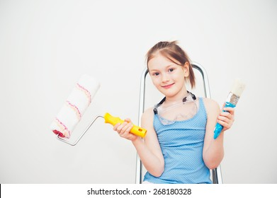 Cute little girl sitting on a step ladder, holding a roller and a brush
