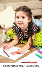 Cute little girl  sitting on floor and drawing picture, on home interior background